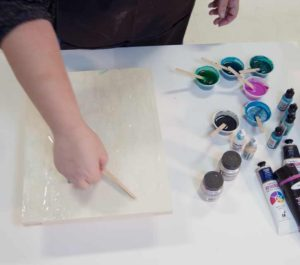 Pour a thin layer of clear resin on the ground and spread it with a popsicle stick.