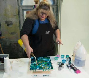 Use the heat gun or blowtorch to heat the resin surface until the colors begin to move and meld. This process also allows bubbles to rise to the surface and pop to make for a smoother surface. Jessica has no fear of the blowtorch!